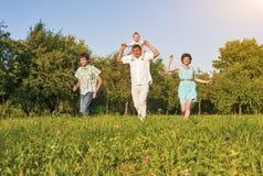 Concept de la famille et idées Famille de quatre heureuse fonctionnant ensemble Image stock