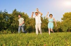 Concept de la famille et idées Famille de quatre heureuse fonctionnant ensemble Image libre de droits
