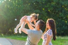 Concept de la famille heureux - fille de père, de mère et d'enfant ayant l'amusement et jouant en nature Images libres de droits