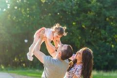 Concept de la famille heureux - fille de père, de mère et d'enfant ayant l'amusement et jouant en nature Photographie stock