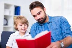 Concept de la famille - jeune père et son petit livre de lecture de fils à Photo libre de droits