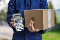 Concept de la livraison de paquet L'homme tient la boîte en carton et le terminal de paiement image libre de droits
