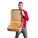 Concept de la livraison de pizza Le jeune homme montre la pizza savoureuse dans la boîte Image stock