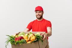 Concept de la livraison : Homme caucasien bel de messager de la livraison d'épicerie dans l'uniforme rouge avec la boîte à épicer image stock