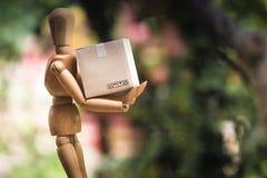 Concept de la livraison : Mannequin en bois tenant le carton de papier d prêt image stock