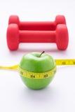 Concept de la perte de poids avec la pomme verte fraîche, la bande de mesure et les haltères Programme de régime de forme physiqu photographie stock libre de droits