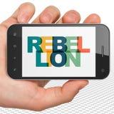 Concept de la politique : Main tenant Smartphone avec la rébellion sur l'affichage Photographie stock libre de droits