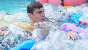 Concept de la pollution de la plan?te Jeunes bains choqués d'homme parmi les déchets clips vidéos