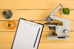 concept de la science - microscope, presse-papiers vide et liquides de produit chimique sur le bureau jaune dans l'amphithéâtre Image stock