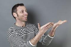 Concept de langage du corps pour l'homme 40s enthousiasmé montrant quelque chose Images stock