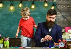 Concept de leçon d'art Le professeur avec la barbe, père enseigne le petit fils à dessiner dans la salle de classe, tableau sur l photos libres de droits