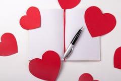 Concept de lettre d'amour - carnet, stylo et coeurs de papier Photo stock
