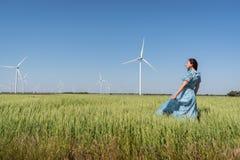 Concept de liberté Belle femme dans la robe bleue sur le champ vert avec les turbines de générateur de vent et le fond de ciel bl images stock