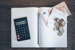 Concept de livre de comptes avec des billets et des pièces d'argent liquide, carnet et calculatrice Image libre de droits