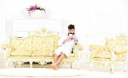 Concept de loisirs d'élite L'homme avec la barbe et la moustache apprécie le matin tout en se reposant sur le sofa de luxe Homme  Image stock