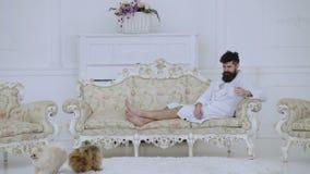 Concept de loisirs d'?lite L'homme somnolent dans le peignoir, boit du café, jeu avec des chiens dans l'hôtel de luxe dans le mat banque de vidéos