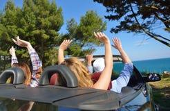 Concept de loisirs, de voyage par la route, de voyage et de personnes - amis heureux conduisant dans la voiture de cabriolet le l Photo libre de droits