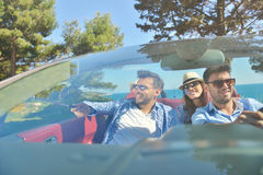 Concept de loisirs, de voyage par la route, de voyage et de personnes - amis heureux conduisant dans la voiture de cabriolet le l Image stock