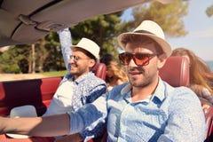Concept de loisirs, de voyage par la route, de voyage et de personnes - amis heureux conduisant dans la voiture de cabriolet le l Photos libres de droits