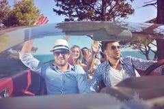Concept de loisirs, de voyage par la route, de voyage et de personnes - amis heureux conduisant dans la voiture de cabriolet le l Photo stock