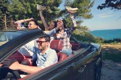Concept de loisirs, de voyage par la route, de voyage et de personnes - amis heureux conduisant dans la voiture de cabriolet le l Photographie stock