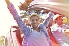 Concept de loisirs, de voyage par la route, de voyage et de personnes - amis heureux conduisant dans la voiture de cabriolet le l Image libre de droits