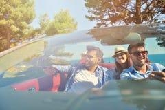 Concept de loisirs, de voyage par la route, de voyage et de personnes - amis heureux conduisant dans la voiture de cabriolet le l Images libres de droits