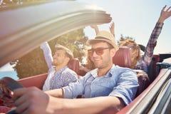 Concept de loisirs, de voyage par la route, de voyage et de personnes - amis heureux conduisant dans la voiture de cabriolet le l Photographie stock libre de droits