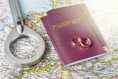 Concept de lune de miel Anneaux de mariage avec des passeports sur la carte images libres de droits