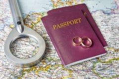 Concept de lune de miel Anneaux de mariage avec des passeports sur la carte photographie stock libre de droits
