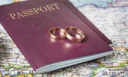 Concept de lune de miel Anneaux de mariage avec des passeports sur la carte images stock