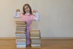 Concept de macht van kennis Een meisje met een stapel van boeken toont haar sterkte Het concept van het onderwijs De ruimte van h stock foto's