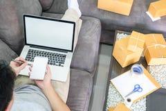 Concept de maison et de mode de vie, achetant utilisant la carte de crédit fonctionnant avec empaqueter le propriétaire de démarr photo stock