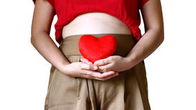 Concept de maternité : femme enceinte touchant son ventre nu et se tenant dans des mains de coeur rouge Photos stock