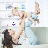 Concept de maternité : mère heureuse jouant avec un bébé an dans la chambre pour des enfants Images libres de droits