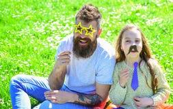 Concept de meilleurs amis Le papa et la fille s'assied sur l'herbe au grassplot, fond vert Enfant et père posant avec Image stock