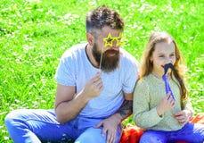 Concept de meilleurs amis Le papa et la fille s'assied sur l'herbe au grassplot, fond vert Enfant et père posant avec Photo libre de droits