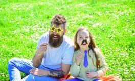 Concept de meilleurs amis Le papa et la fille s'assied sur l'herbe au grassplot, fond vert La famille dépensent des loisirs dehor Photo libre de droits