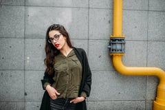 Concept de mode : belle jeune fille avec de longs cheveux, verres, lèvres rouges se tenant près du mur moderne portant dans le co Photo libre de droits