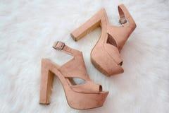 Concept de mode Chaussures beiges de suède avec des talons sur une fourrure artificielle blanche photos libres de droits
