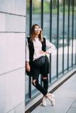 Concept de mode de rue - femme mince assez jeune dans le style de noir de roche posant contre le mur photographie stock libre de droits