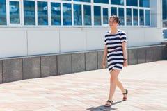 Concept de mode de rue Jeune beau femme dans la ville Belle fille portant la robe barrée marchant sur la rue photo libre de droits