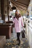 Concept de mode de rue : plein portrait de corps de la jeune belle femme portant le manteau rose avec le sac à main marchant dans Photographie stock libre de droits