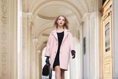Concept de mode de rue : portrait de la jeune belle femme portant le manteau rose avec le sac à main marchant dans la ville modèl Images libres de droits