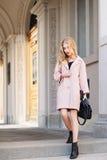 Concept de mode de rue : portrait de la jeune belle femme portant le manteau rose avec le sac à main marchant dans la ville vieux Photographie stock libre de droits