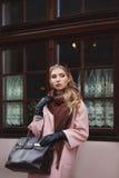 Concept de mode de rue : portrait de la jeune belle femme portant le manteau rose avec le sac à main posant à la fenêtre Ville Photographie stock