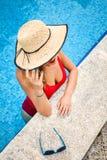 Concept de mode de vacances d'été - belle jeune femme dans la piscine un jour ensoleillé d'été photographie stock libre de droits