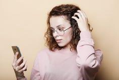 Concept de mode de vie, émotif et de personnes : Jeune belle femme bouclée avec le smartphone image stock