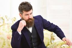 Concept de mode de vie d'élite L'homme avec la barbe et la moustache portant le costume classique, s'assied sur le fauteuil ou le Photographie stock