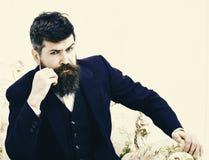 Concept de mode de vie d'élite L'homme avec la barbe et la moustache portant le costume classique, s'assied sur le fauteuil ou le Images libres de droits